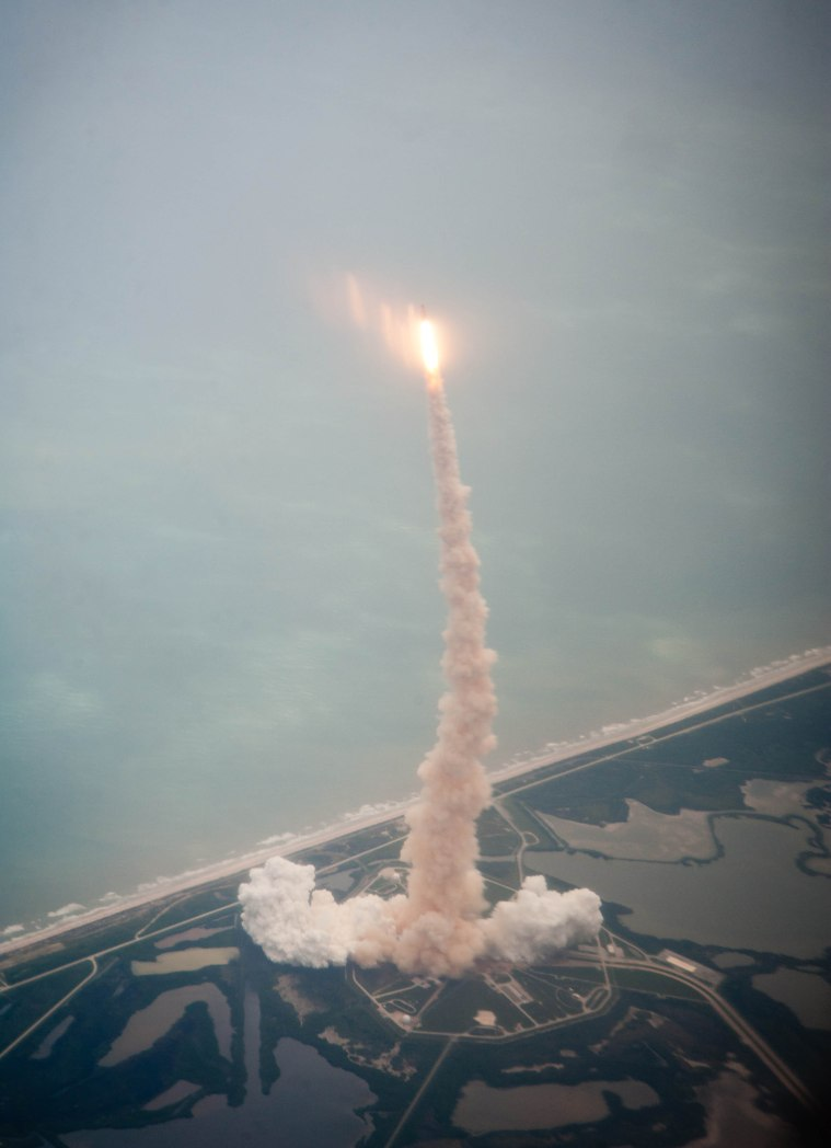 Space shuttle Atlantis is seen through the window of a Shuttle Training Aircraft (STA) as it launches from launch pad 39A at Kennedy Space Center on the STS-135 mission, Friday, July 8, 2011 in Cape Canaveral, Fla. Atlantis launched on the final flight of the shuttle program on a 12-day mission to the International Space Station. The STS-135 crew will deliver the Raffaello multipurpose logistics module containing supplies and spare parts for the space station. Photo Credit: (NASA/Dick Clark)