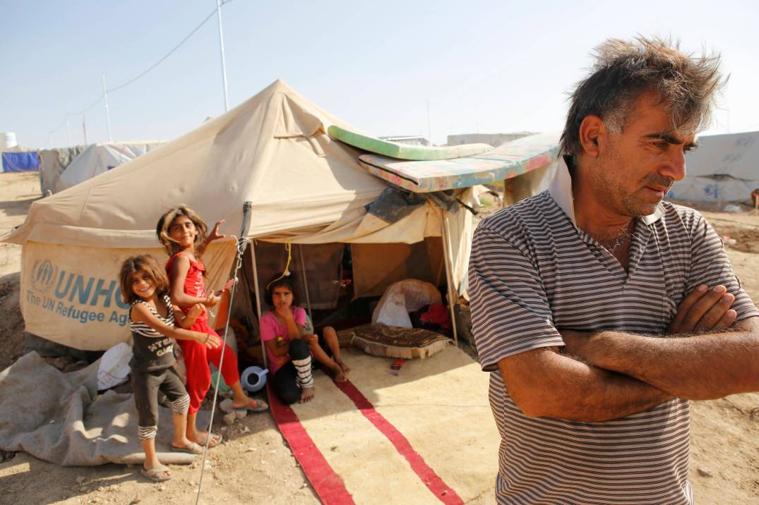 A Syrian refugee, who fled from the violence in Syria, stands outside a tent as his children look on, at the Domiz refugee camp in the northern Iraqi of province Dohuk July 3, 2013. Picture taken July 3, 2013. REUTERS/Ahmad Mousa  (IRAQ - Tags: CONFLICT CIVIL UNREST SOCIETY IMMIGRATION)